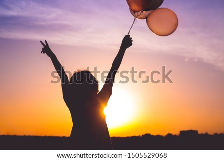 Silhouette of female holding bunch of balloons in raised arms and gesturing V sign against bright sundown sky #1505529068