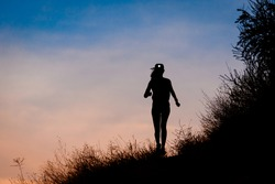 Silhouette of female running on a side of a hill on trail during dawn or dusk with beautiful sky in the background wearing a headlamp or head lamp.