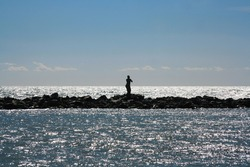 Silhouette of female statue, on the cliff in the sea, with blue sky.