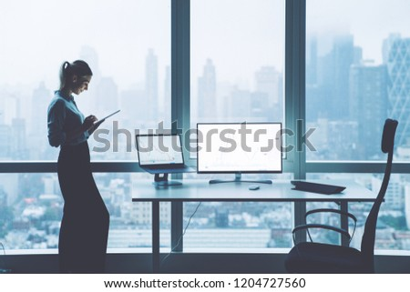 Silhouette of female trade manager checking currency exchange via tablet standing in office interior next to skyscraper window. Mock up copy space monitor for financial information. Success concept