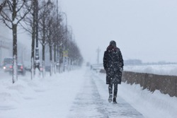 Silhouette of female walking on the street during snowfall, view from the back/ Selective soft focus on snowflakes/ heavy snowfall at St. Petersburg Russia/ Winter in St. Petersburg