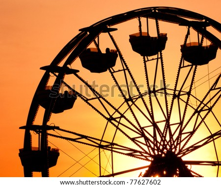 Silhouette of ferris wheel at sunset at county fair.