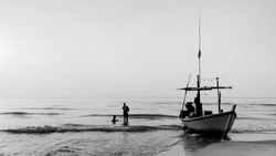 Silhouette of fisherman and boat in gulf of Thailand.Scenery of nature morning sunrise.Beautiful scenery at Hua Hin old town in Thailand.black and white.