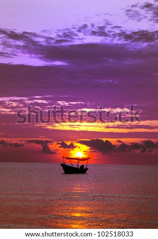 Silhouette of fisherman boat during sunrise.