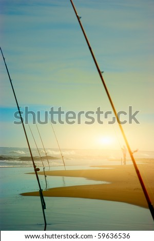 Silhouette of fisherman catching at sunset on the beach