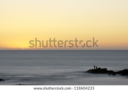 Silhouette of fisherman fishing at sunset at the ocean - stock photo