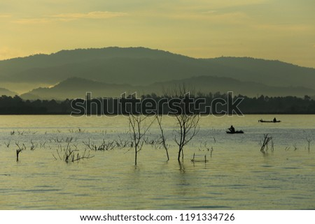 Silhouette of fisherman make a living and activities on boat in the morning at Bangpra reservoir, Chonburi , Thailand  #1191334726