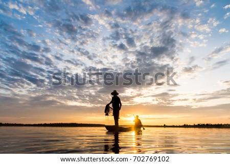Silhouette of Fishermen throwing net fishing in sunset time at Wanon Niwat district Sakon Nakhon Northeast Thailand. #702769102