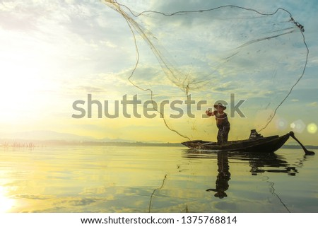 Silhouette of fishermen using coop-like trap catching fish in lake with beautiful scenery of nature morning sunrise. Beautiful scenery at Bang-Pra, Chonburi Province Thailand. #1375768814