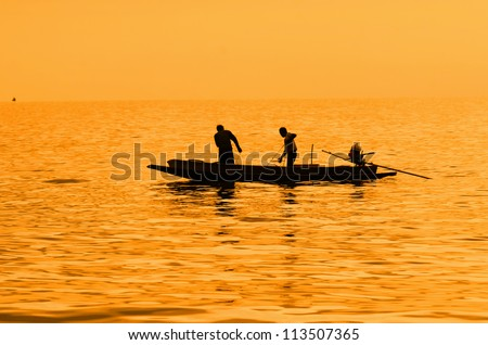 silhouette of fishermen with yellow and orange background