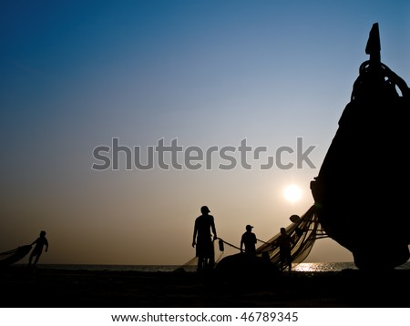 Silhouette of fishers boat against a sunset and blue sky on the sea