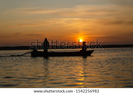 Silhouette of fishing boat and fisherman  in the sunrise on the lake in the sunrise .