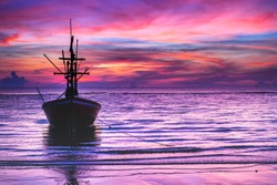 Silhouette of fishing boat in tropical sea at beautiful sunrise, Ultra violet, pink twilight sky background.
