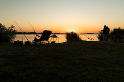 Silhouette of fishing tackle at sunrise. Silhouette of a fisherman at sunrise. Sunrise by the lake.