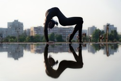 Silhouette of flexible and fit girl bending her back. Concept of yoga and healthy lifestyle