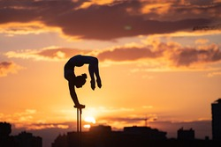 Silhouette of flexible and fit girl doing handstand and keeping balance against dramatic unset. Concept of yoga and healthy lifestyle