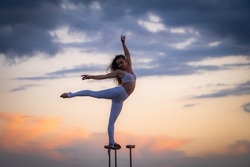 Silhouette of flexible and fit girl standing on fit with split and keeping balance against dramatic sunset Concept of yoga and healthy lifestyle