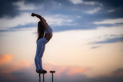Silhouette of flexible and fit girl standing on fits with split and keeping balance against dramatic sky during sunset Concept of yoga and healthy lifestyle