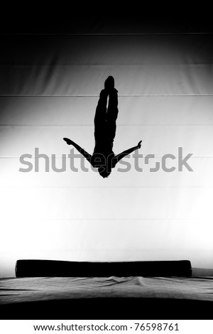 silhouette of flying man on trampoline