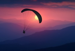 Silhouette of flying paraglide in a light of sunrise above the misty mountain valley.