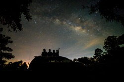 Silhouette of four friends watching milky way and pointing to the star on roof top of SUV car