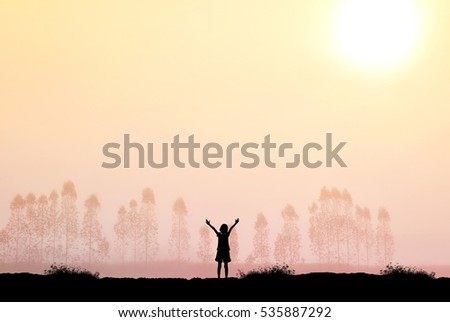 Silhouette of freedom girl in sunrise background.