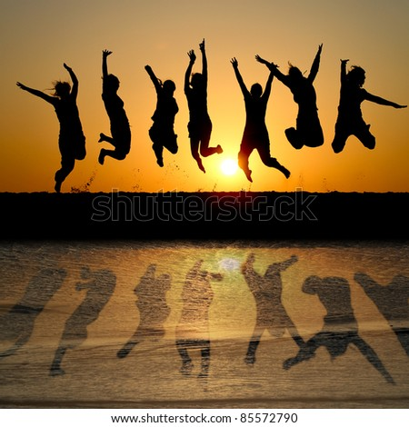 silhouette of friends jumping in sunset at beach with reflection in water