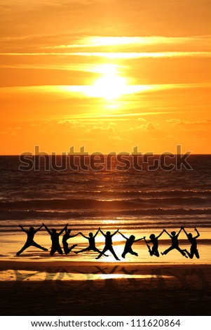 silhouette of friends jumping on beach in sunset light