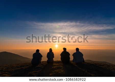 silhouette of friends  sitting together watching sunset for business successful and team work concept.