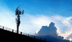 Silhouette of 5G smart mobile cellular network telephone radio network antenna base station on the telecommunication mast radiating signal.