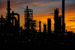Silhouette of gas distillation of tank oil refinery plant tower and column tank oil of Petrochemistry industry on sky sunset background