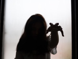 silhouette of ghost crawling hand from window