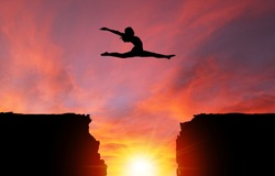 Silhouette of girl dancer in a split leap over dangerous cliffs with sunset or sunrise background and copy space. Concept of faith, conquering adversity, taking risk; challenge, courage, determination