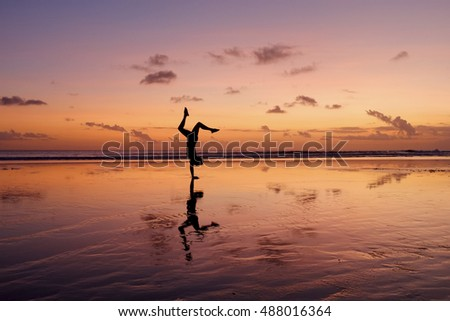 Silhouette of girl doing handstand on beach at sunset - Bali, Indonesia