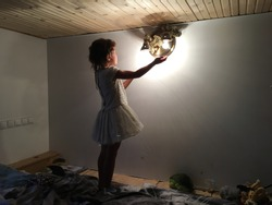 silhouette of girl in a white dress holding out her hands to the light