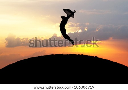 silhouette of girl jumps with umbrella in sunset #106006919
