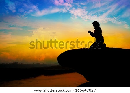 Silhouette of girl praying on the hill