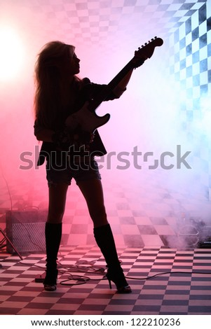Silhouette of girl standing and playing electric guitar in studio in smoke and pink light.