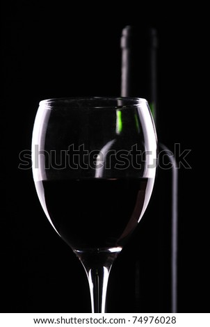 Silhouette of glasses and bottles of wine on a dark background