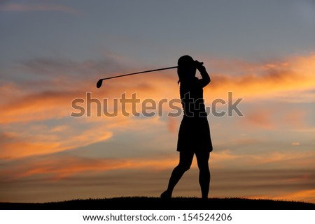 Silhouette of golfer swinging.