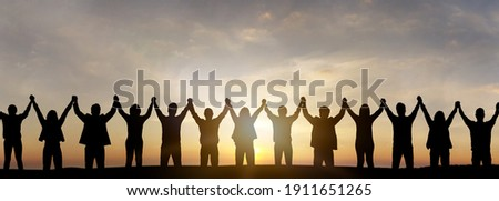 Silhouette of group happy business team making high hands over head in sunset sky background for business teamwork concept. Photo stock ©