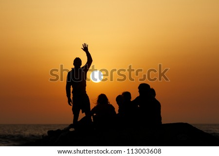 silhouette of group in sunset at beach