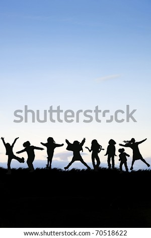 Silhouette of group of children jumping in the air against vivid sunset sky