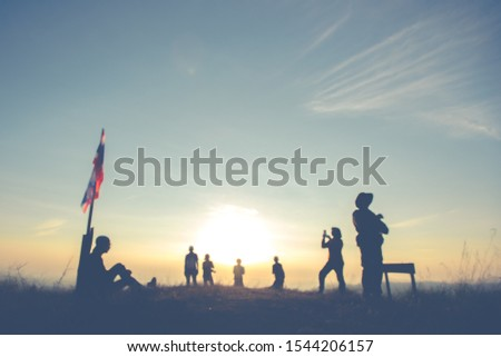 Silhouette of group of friends relaxing and standing after long day for trekking with sunrise background. Trekking Concept. #1544206157