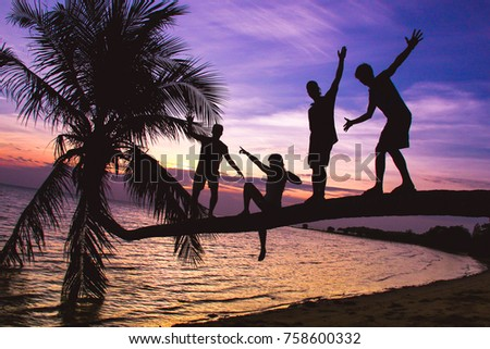 Stock Photo Silhouette of group of friends standing in balance on reclining palm tree by the beach with amazing purple sky at sunset on the background in the island of Koh Phangan, Thailand