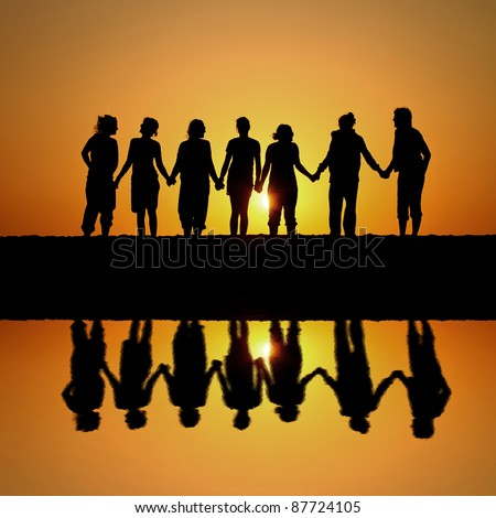 silhouette of group of friends standing in sunset at beach with reflection