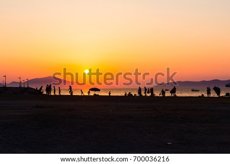 Stock Photo Silhouette of group of friends, young people, until they are having fun on the beach playing soccer.