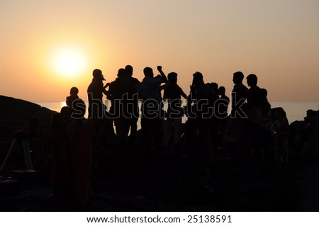 Silhouette of group of people dancing at sunset near the sea - stock photo
