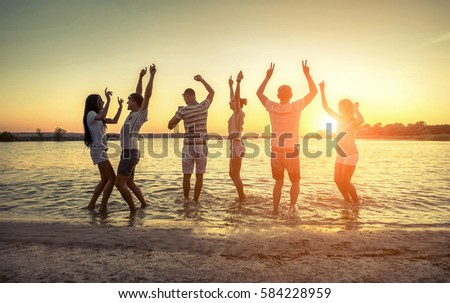 Silhouette of group young people on the beach under sunset sky with clouds at summer evening.