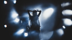 Silhouette of guitar player / guitarist / girl / woman perform on concert stage. Dark background, smoke, concert  spotlights
